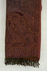 Juniper Hearth pure wool reversible tasseled throw rug with classic paisley design in shades of purple, burgundy and olive, with highlights in burnt orange.