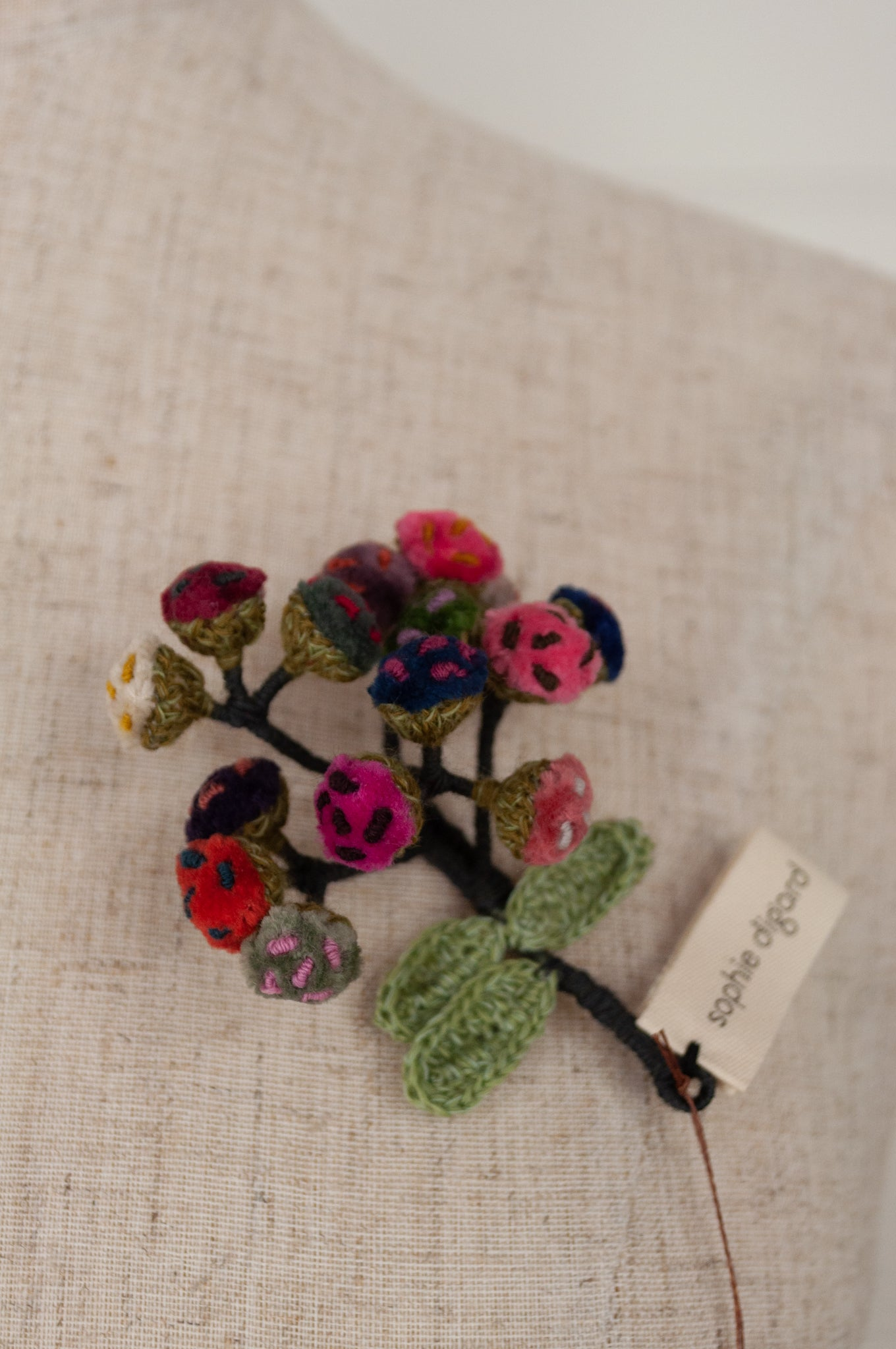 Sophie Digard Immortelle velvet brooch in bright wintery tones of pink, red, blue and green.