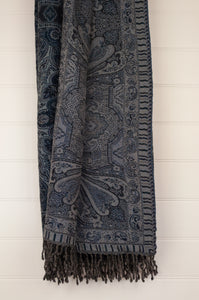 Juniper Hearth pure wool reversible tasseled throw in a paisley design, shades of sapphire blue and light grey.