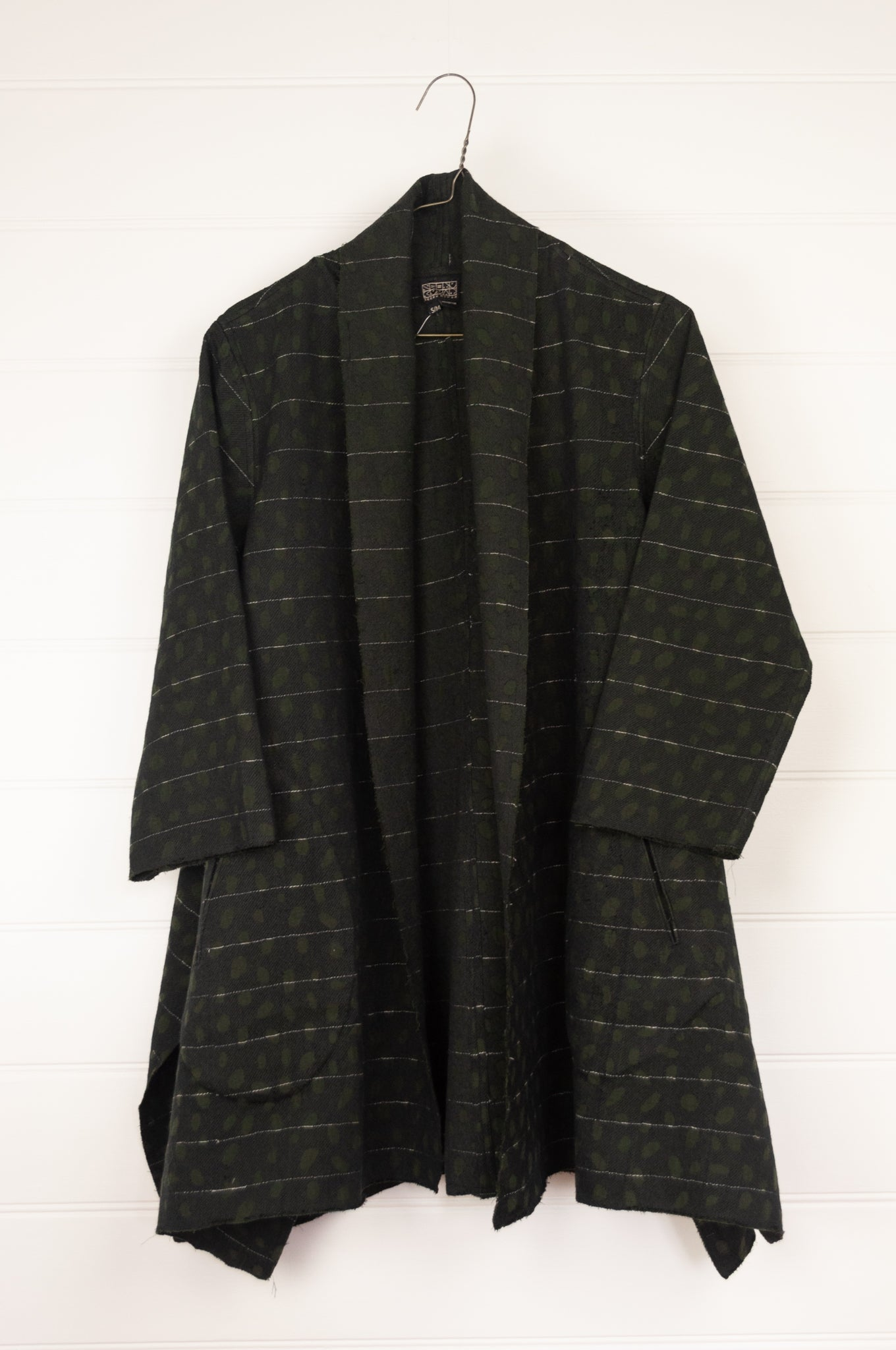 Neeru Kumar Karlens jacket in handloomed cotton jacquard, olive on black with white thread highlights, raw edges to seams, swing A-line shape with shawl collar, pockets and side splits.