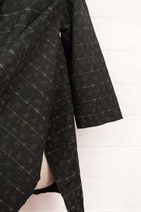Neeru Kumar Karlens jacket in handloomed cotton jacquard, olive on black with white thread highlights, raw edges to seams, swing A-line shape with shawl collar, pockets and side splits (close up showing side splits).