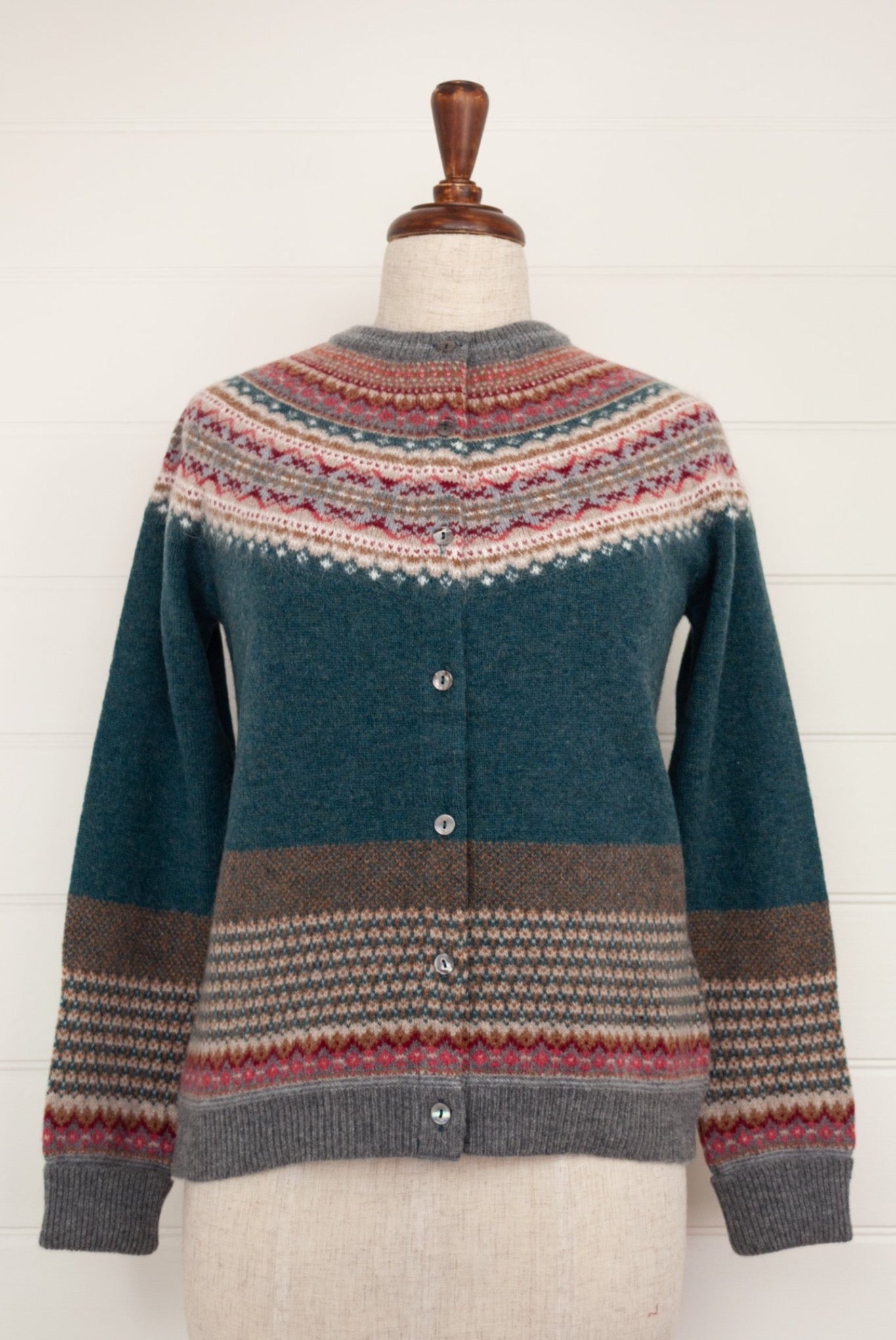Eribé Alpine cardigan in Lugano, features a rich teal body, with highlights in rust, burgundy, bright pink, ecru and soft blue grey.