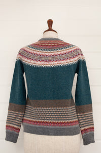 Eribé Alpine sweater in Lugano, features a rich teal body, with highlights in rust, burgundy, bright pink, ecru and soft blue grey.
