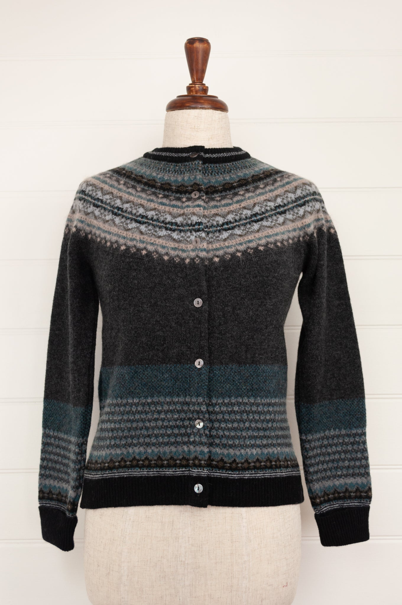 Eribé Alpine fairisle cardigan in Colliery, charcoal background, with accents in shades of oatmeal, teal, and soft blue greys