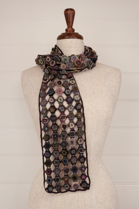 Sophie Digard Paris crochet scarf in merino wool, Magnolia, lace work flowers in relief in shades of navy, pink, taupe, teal and light blue on a coffee brown ground.