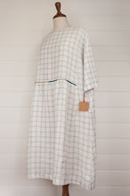 Load image into Gallery viewer, Dve Collection Padma dress in pure linen, ecru white with indigo windowpane check, selvedge edge detailing, hand embroidered at waist, one size three quarter sleeves (side view).