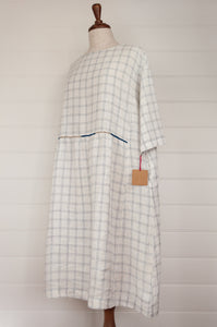 Dve Collection Padma dress in pure linen, ecru white with indigo windowpane check, selvedge edge detailing, hand embroidered at waist, one size three quarter sleeves (side view).