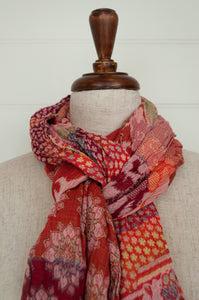 Létol scarf made in France from organic cotton, jacquard weave Donatello Pomelo, a fabulous floral and geometric design in rich reds, crimson, orange, pink, yellow with highlights of turquoise.