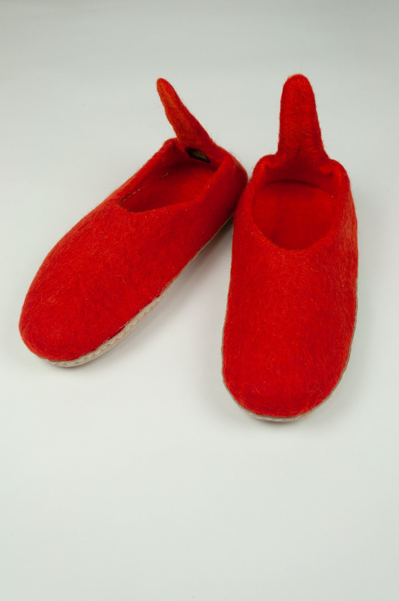 Fair trade wool felt slippers pull on style with heel tab in orange red.
