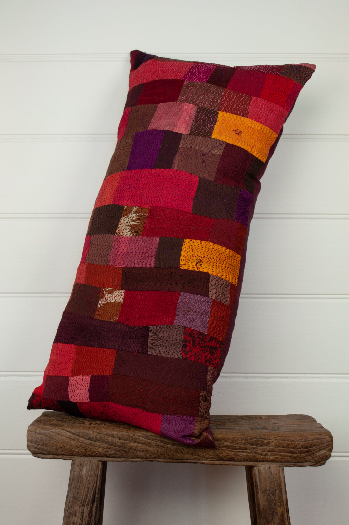 Vintage silk kantha bolster cushion, feather insert included, in shades of cherry red, rose, chocolate and gold.