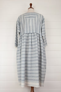 Maku Textiles Sefid dress in blue and white striped khadi cotton, one size loose fitting tunic dress with three quarter sleeves, front slit neck opening and gathered skirt and side pockets (back view).