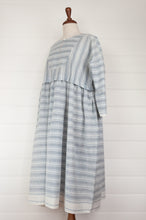 Load image into Gallery viewer, Maku Textiles Sefid dress in blue and white striped khadi cotton, one size loose fitting tunic dress with three quarter sleeves, front slit neck opening and gathered skirt and side pockets (side view).