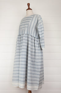 Maku Textiles Sefid dress in blue and white striped khadi cotton, one size loose fitting tunic dress with three quarter sleeves, front slit neck opening and gathered skirt and side pockets (side view).