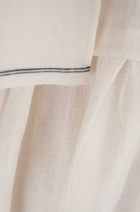 Maku Textiles Sefid dress in natural white cotton linen, one size loose fitting tunic dress with three quarter sleeves, front slit neck opening and gathered skirt and side pockets (selvedge edge detail).