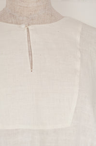 Maku Textiles Sefid dress in natural white cotton linen, one size loose fitting tunic dress with three quarter sleeves, front slit neck opening and gathered skirt and side pockets (detail).