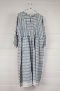 Maku Textiles Sefid dress in blue and white striped khadi cotton, one size loose fitting tunic dress with three quarter sleeves, front slit neck opening and gathered skirt and side pockets.