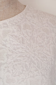 Dve Kamakshi top in fine white cotton with hand embroidered white on white chikankari panel on button up bodice, gathers at sides, sleeveless.
