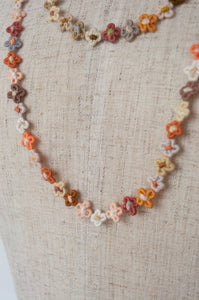 Sophie Digard delicate, long necklace is made from a string of tiny handmade flowers formed in linen thread in the Sesam palette, earthy tones of coral, gold, blush, chocolate, grey, terracotta and gold.
