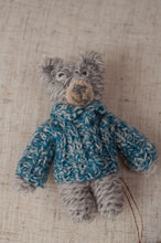 Load image into Gallery viewer, Sophie Digard hand crocheted and knitted tiny wool bear brooch, grey teddy with blue jumper.