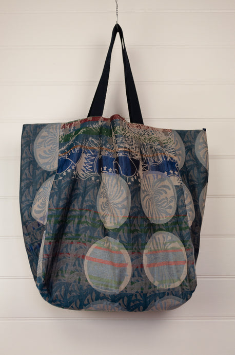Létol made in France organic cotton reversible large tote bag, jacquard pattern in shades of turquoise, blue, with highlights in red, geometric pattern reverse in co-ordinating tones.