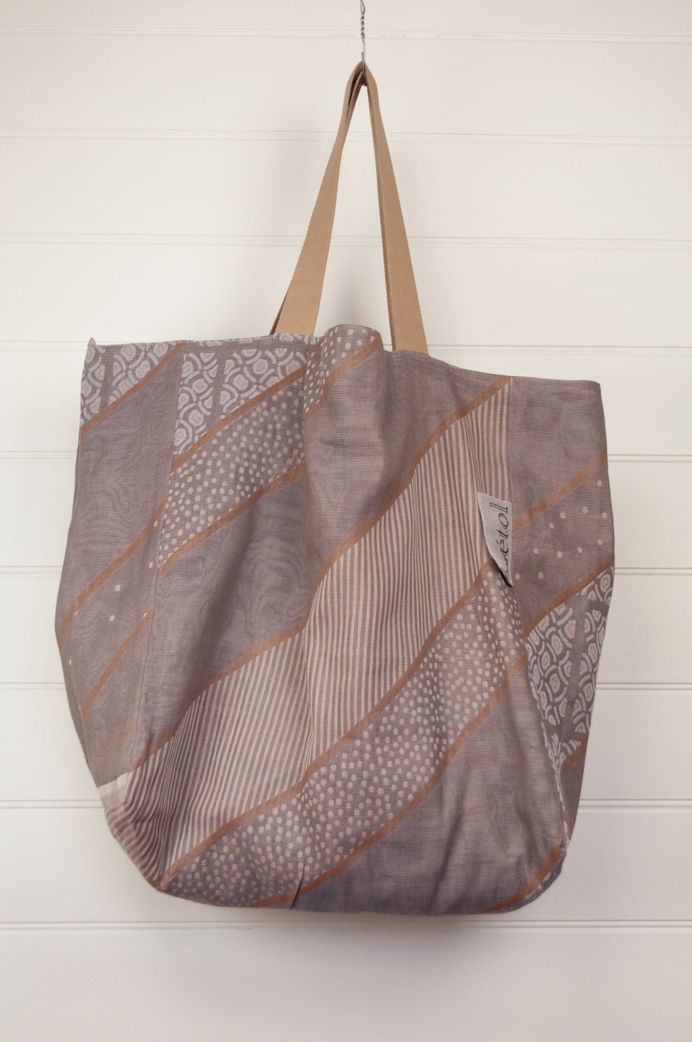 large Létol reversible large tote bag made in France from organic cotton, has a striking geometric design in pewter and bronze, and on the reverse a co-ordinating design in similar tones with highlights in coral, olive and denim.