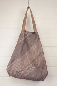 Létol reversible large tote bag made in France from organic cotton, has a striking geometric design in pewter and bronze, and on the reverse a co-ordinating design in similar tones with highlights in coral, olive and denim.