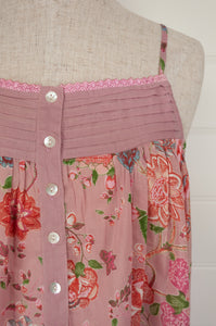Ethically made cotton nightdress nightiescreen printed with large pink, coral and rose red flowers with highlights in denim blue, vanilla and leaf green on a soft rose pink background.