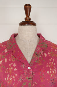 Ethically made cotton voile pyjamas with garden flowers of pink, red and vanilla on a deep raspberry pink red background.