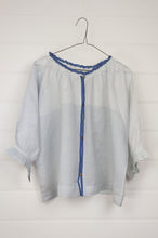 Load image into Gallery viewer, Runaway Bicycle button up silk blouse in blue on white fine stripe and check with blue selvedge detailing, subtly frill at gathered neck, elbow length sleeves gathered to frill at cuff.