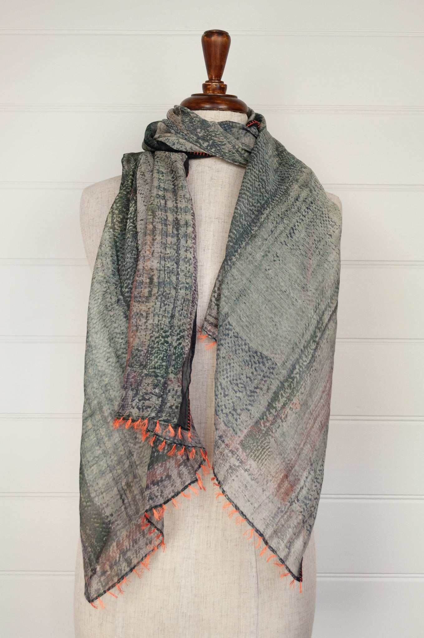 Neeru Kumar digital print cotton silk scarf in shades of grey green and silver with orange button hole edge stitching and tassels.