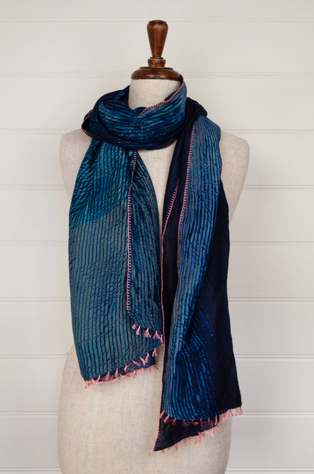 Neeru Kumar shibori dyed silk scarf in navy and tons of blue and turquoise with pink button hole edge stitching and tassels.