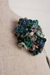 Sophie Digard handmade, embroidered and crocheted linen flower brooch in shades teal, aqua, mint and blue.