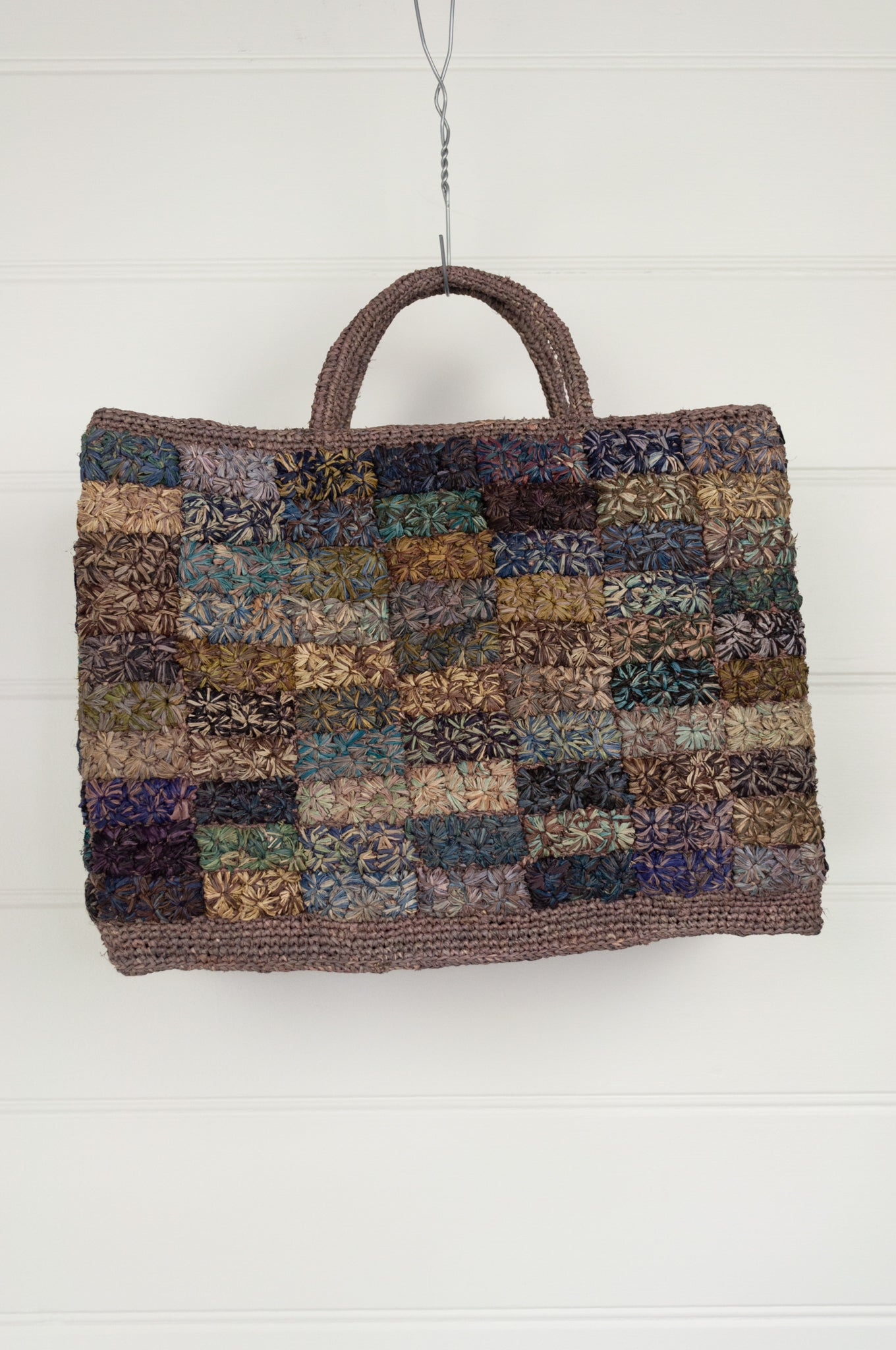 Sophie Digard hand woven macrame raffia bag is a patchwork of subtle tones of olive, coffee, teal and lilac.