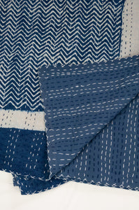 Block printed in indigo, blue and white kantha quilt hand made in Jaipur, featuring chevron pattern and plain blue and white border.