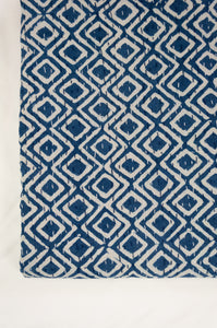 Block printed in indigo, blue and white kantha quilt hand made in Jaipur, featuring diamond pattern and plain blue and white border.
