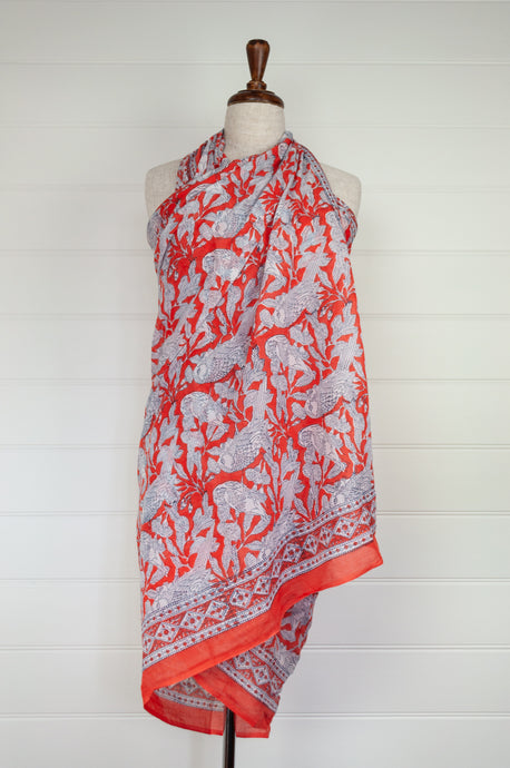 Cotton voile sarong, block printed by hand. Cheeky white parrots on a rich tangerine orange base.