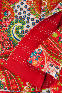 Handstitched cotton kantha quilt, a colourful paisley on a brilliant red background, with highlights in lime, emerald, turquoise, white, and tan