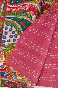 Handstitched cotton kantha quilt, a colourful paisley on a deep pink background, with highlights in lime, emerald, turquoise, white, and tan