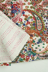 Handstitched cotton Kantha quilt paisley on a white background, with highlights in olive green, emerald, red, navy blue and tan