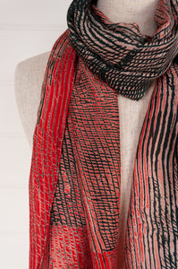 Neeru Kumar shibori silk scarf in shades of coral and charcoal black with handmade coral tassels.