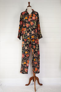 Ethically made cotton voile pyjamas, tropical print of red, gold and orange flowers on black background.