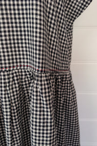 DVE black and white gingham check Toshni dress in handloom cotton, easy fit round neck short sleeve bodice with gathered skirt and in seam pockets.