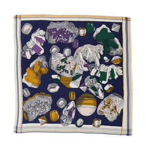 Inouitoosh silk and modal square scarf 130 x 130 cm, Piotr, depicting gems and uncut gems on a navy background in shades of mustard gold, amethyst  and emerald.