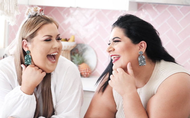 Two women wearing statement earrings laughing together.