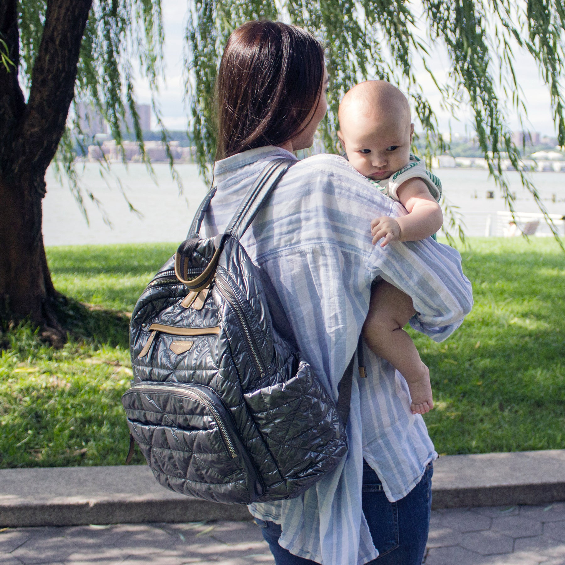 Woman wearing the Pewter companion backpack holding a baby.