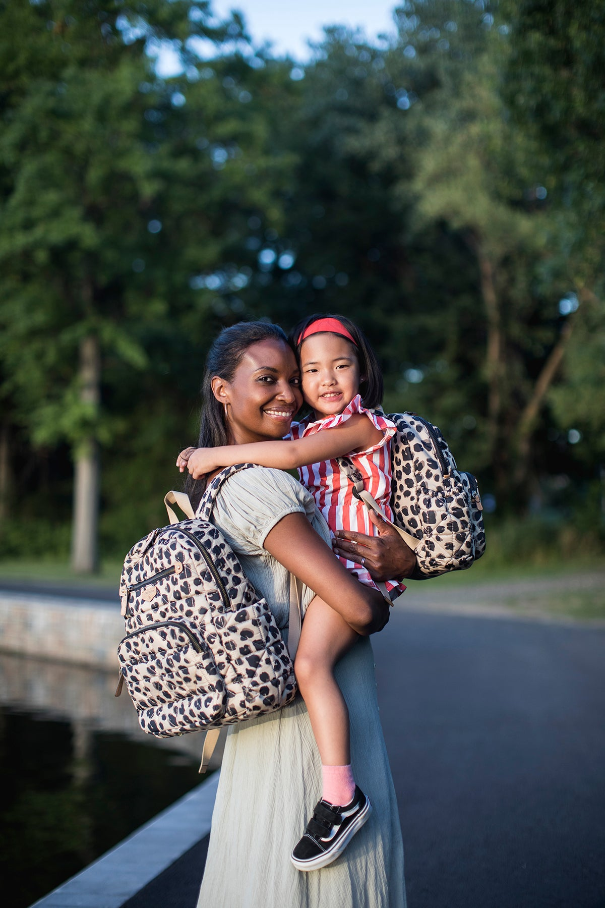 Woman wearing leopard companion backpack holding little girl that is also wearing a leopard backpack