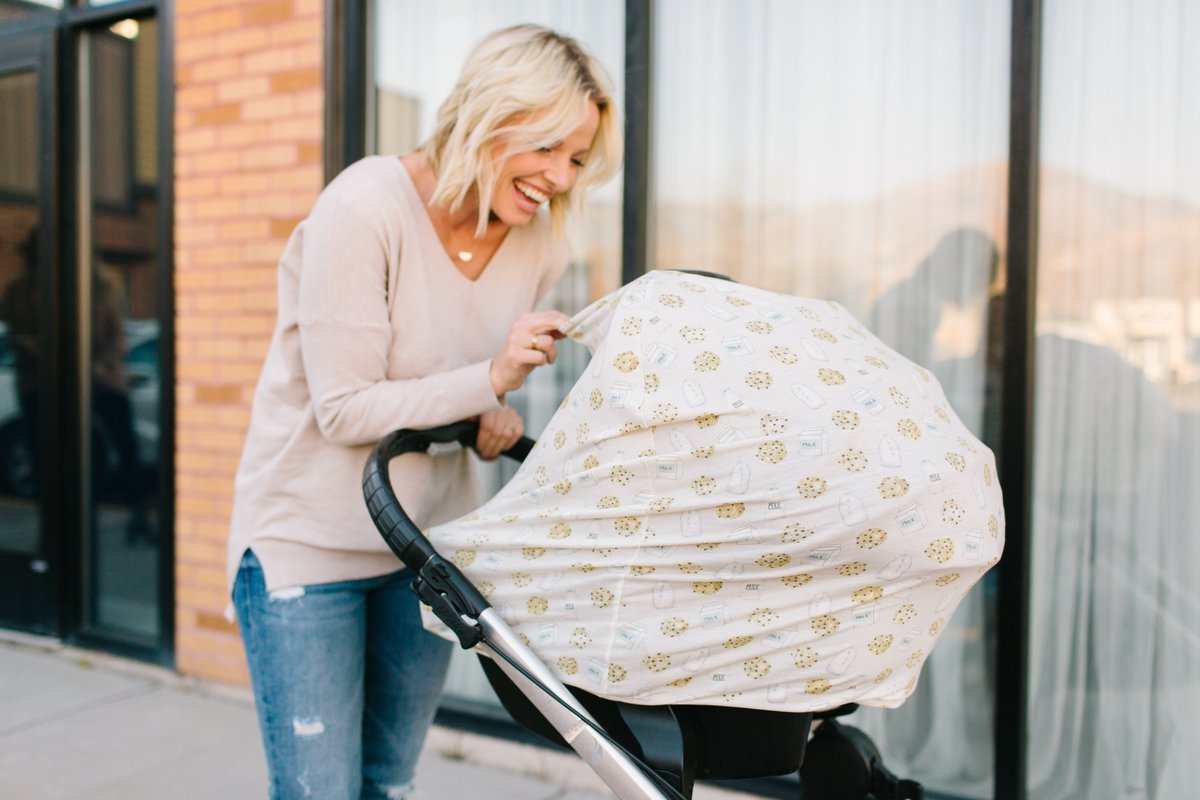 Mother pushing stroller with car seat covered in a Chip multi-use cover