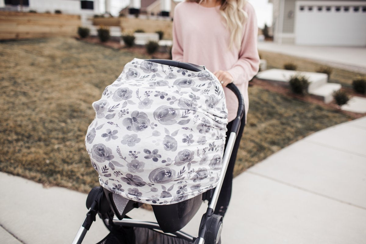 Mother pushing stroller with car seat covered in a Rowan multi-use cover