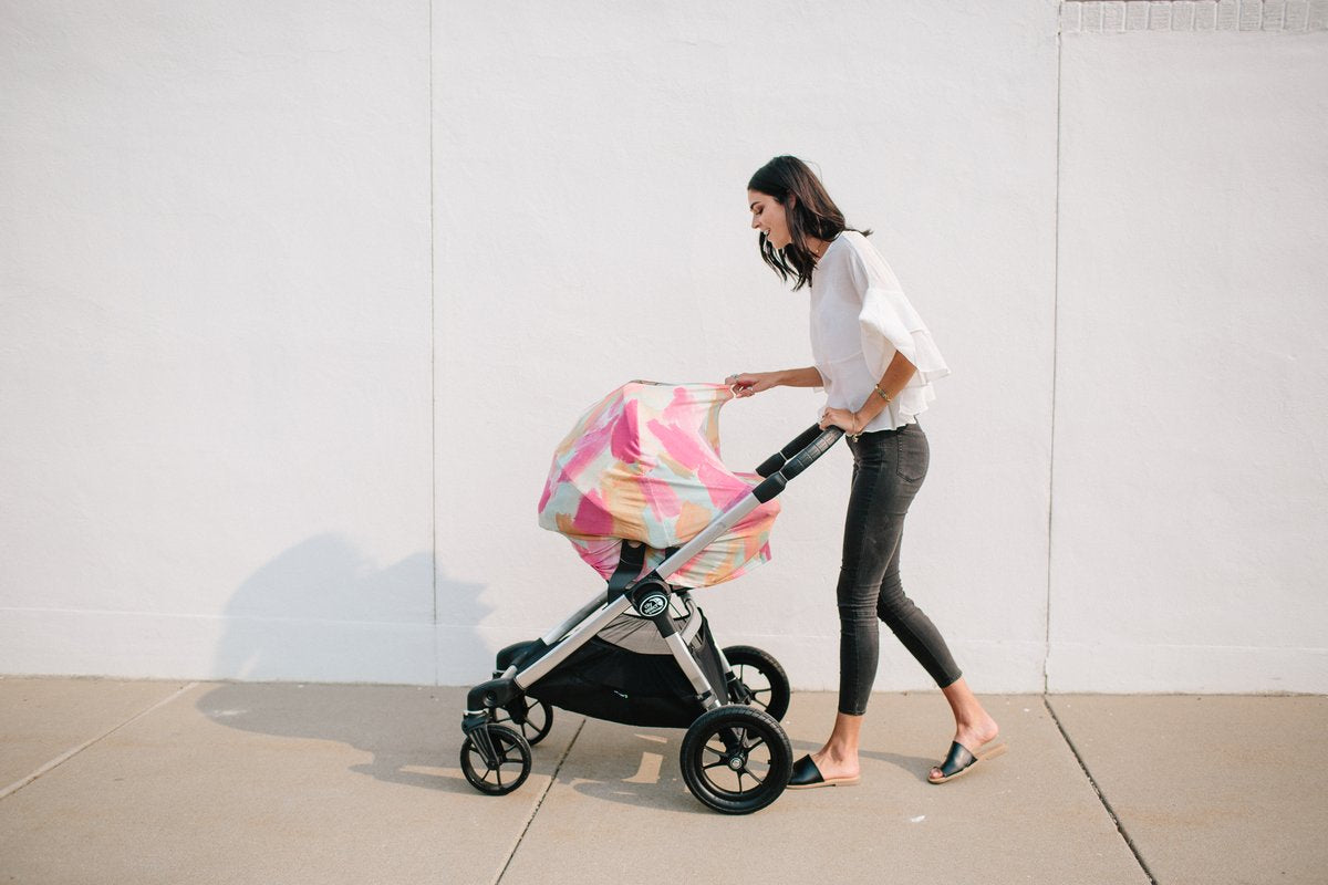 Mother pushing stroller with car seat covered in a Monet multi-use cover