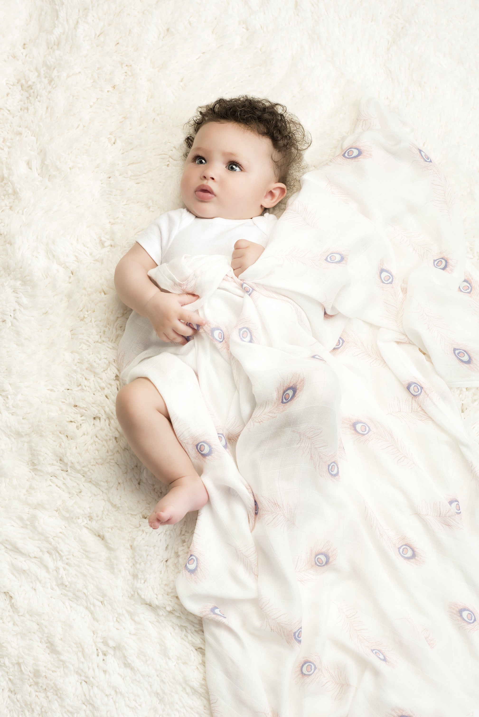 Baby laying on fur rug covered up in a featherlight silky soft swaddle.